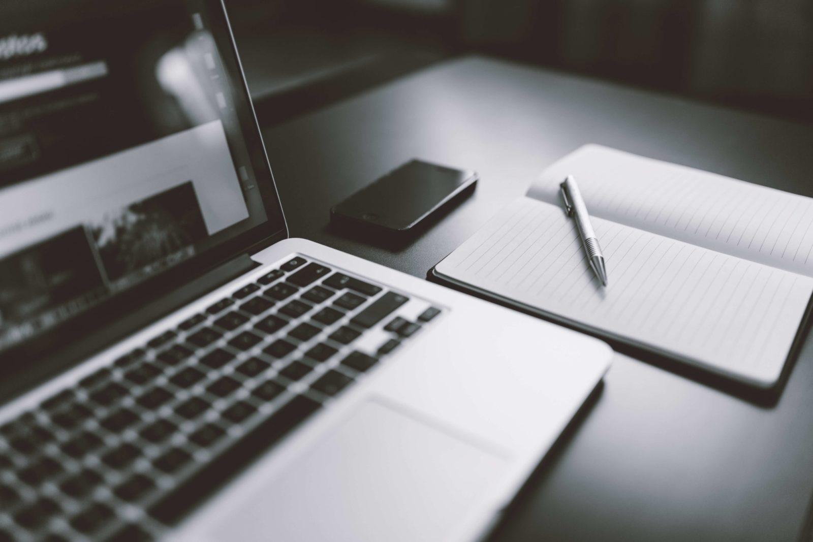 Ein Laptop mit Notizbuch. Ein gutes Setup zum lernen fürs Informatikstudium.