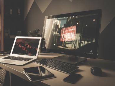 Ein Laptop und ein Computerbildschirm auf einem Schreibtisch