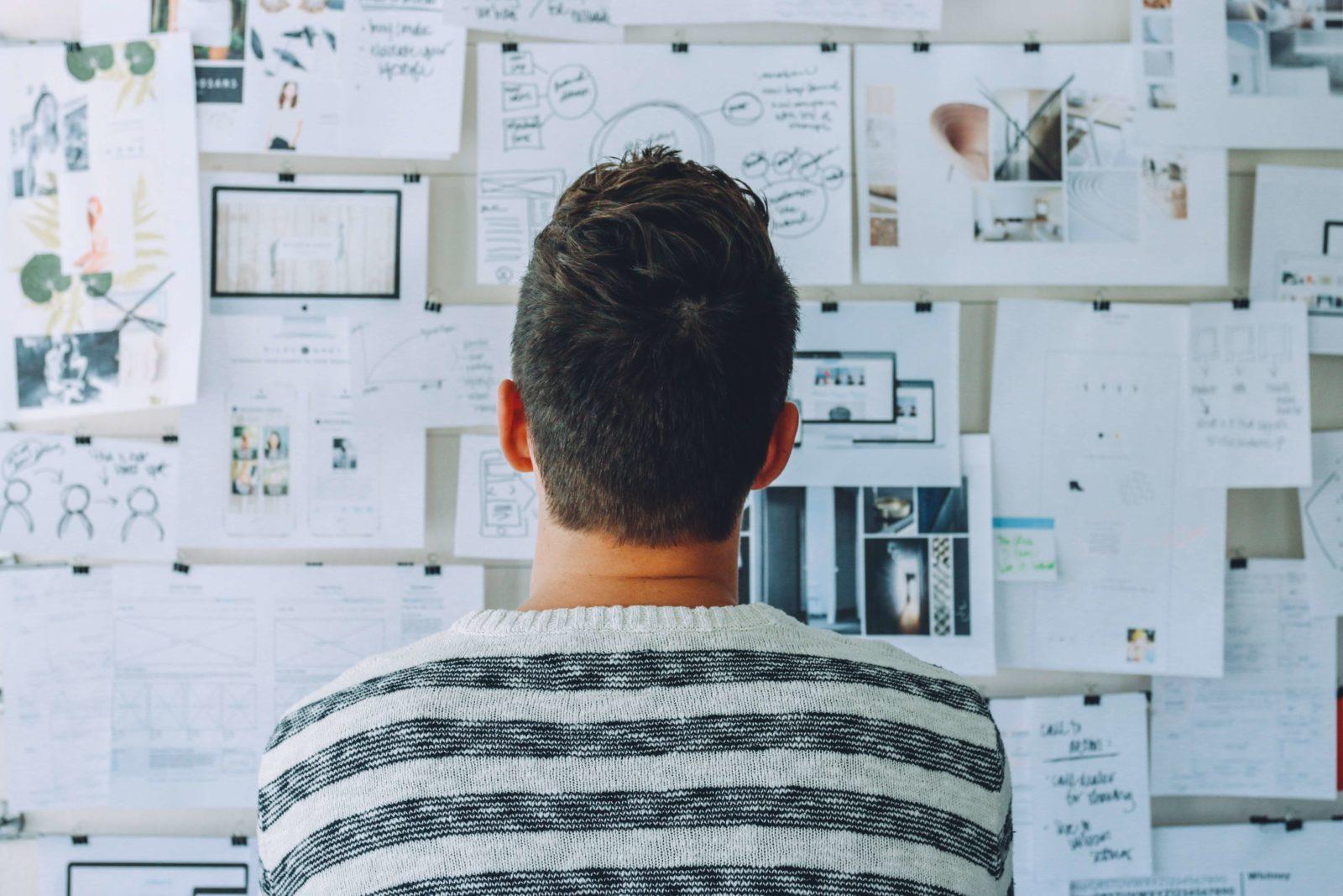 Ein Mann welcher vor einer Wand mit angehefteten Notizen steht und diese liest.