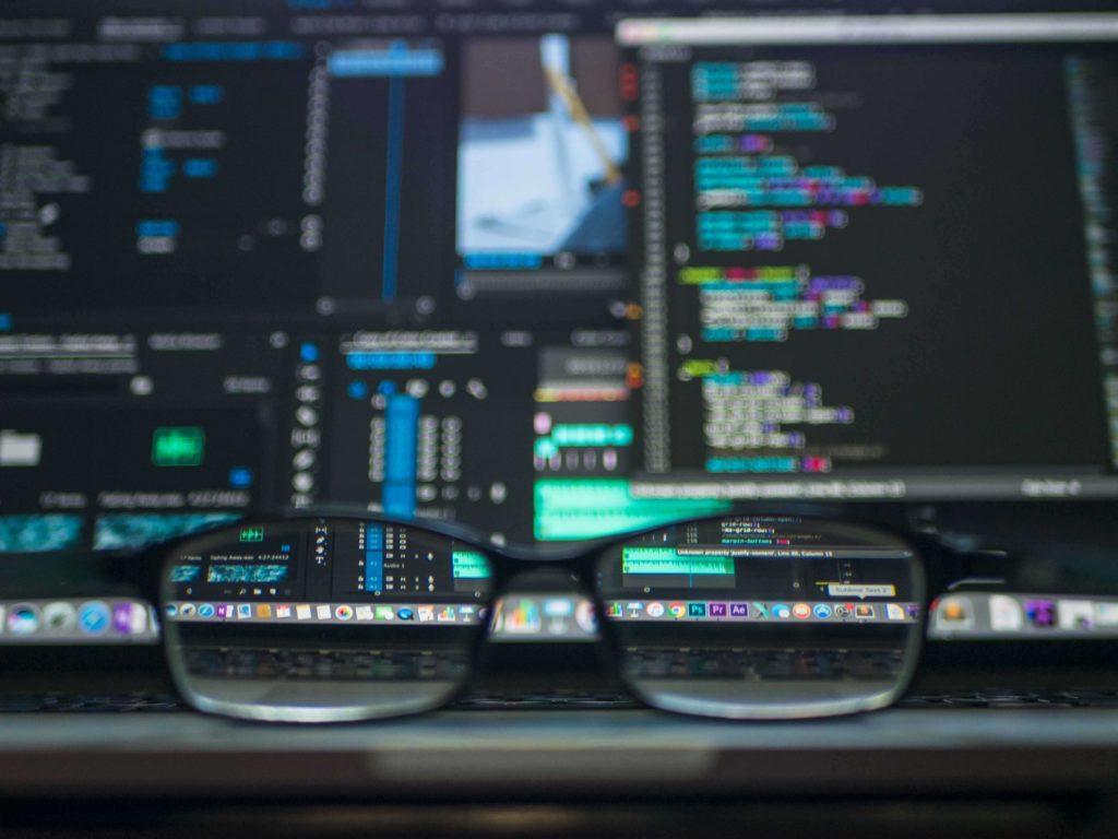 Eine Brille vor einem Bildschirm mit einer Entwicklungsumgebung und Code