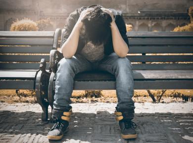 Ein Student sitzt mit den Armen über den Kopf verschränkt auf einer Bank