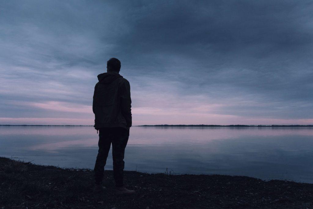 Ein Student steht alleine am Strand