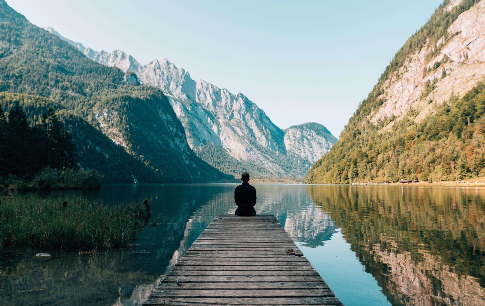Ein Mensch meditiert auf einem Steg vor einem See
