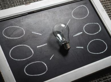 Eine Glühbirne auf einer Tafel, mit Gedankenblasen außen herrum