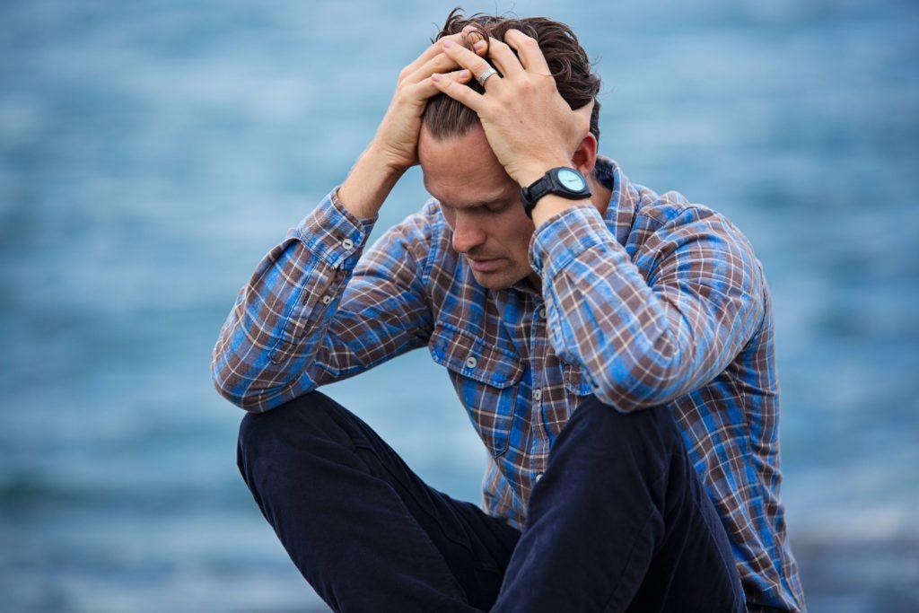 Das Bild zeigt einen Mann, welcher sich verzweifelt an die Stirn fässt.