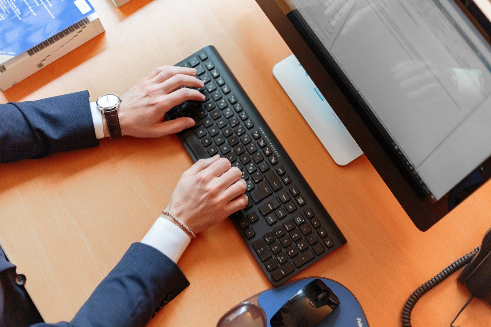 Eine Tastatur, ein Bildschirm und zwei Hände welche auf der Tastatur liegen.
