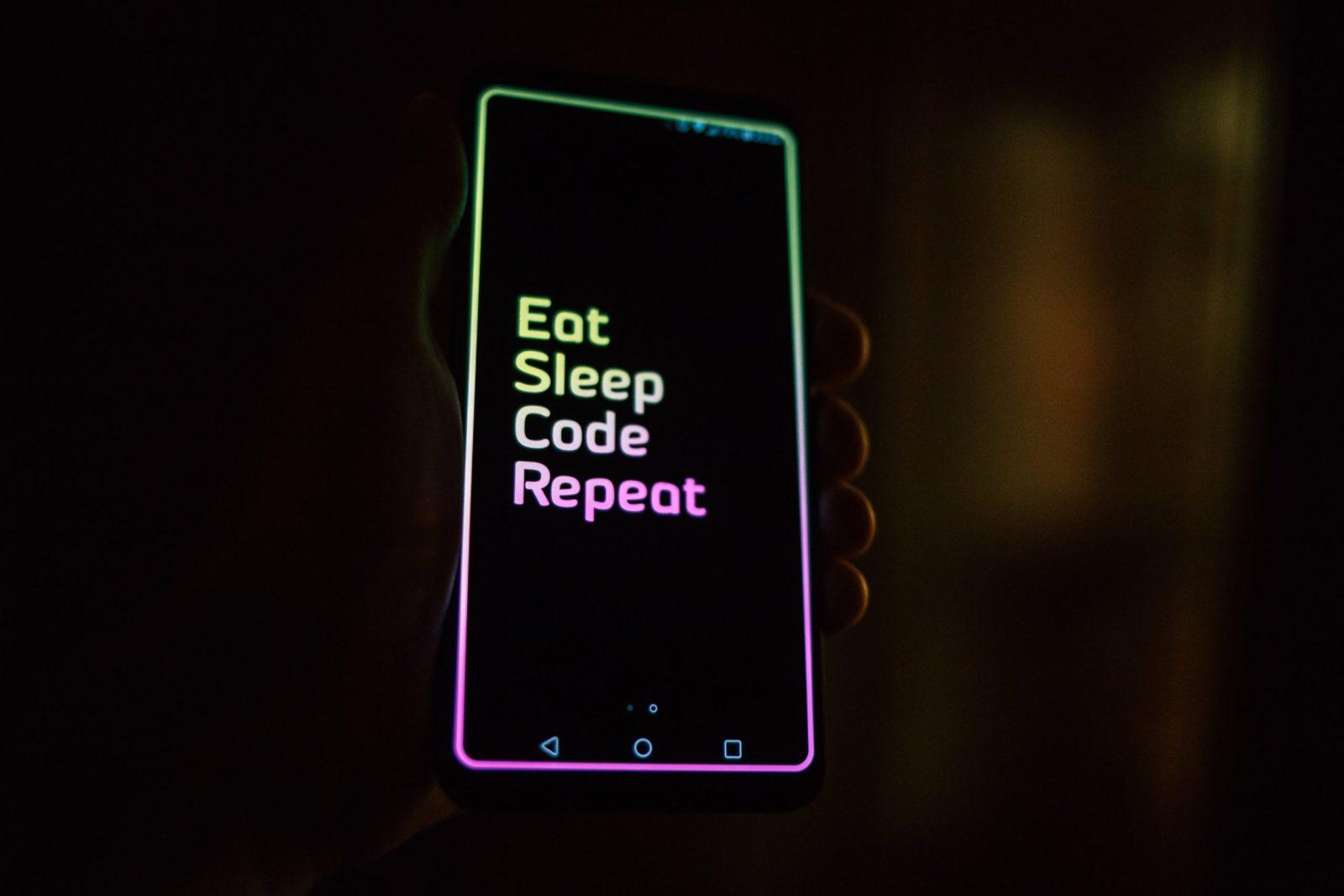 """Das Bild zeigt ein Smartphone mit dem Text """"Eat Sleep Code Repeat"""" auf dem Bildschirm."""